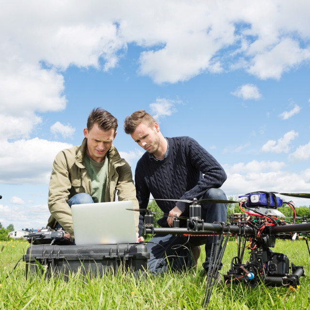 """Technicians Working On Laptop By UAV in Park"" stock image"