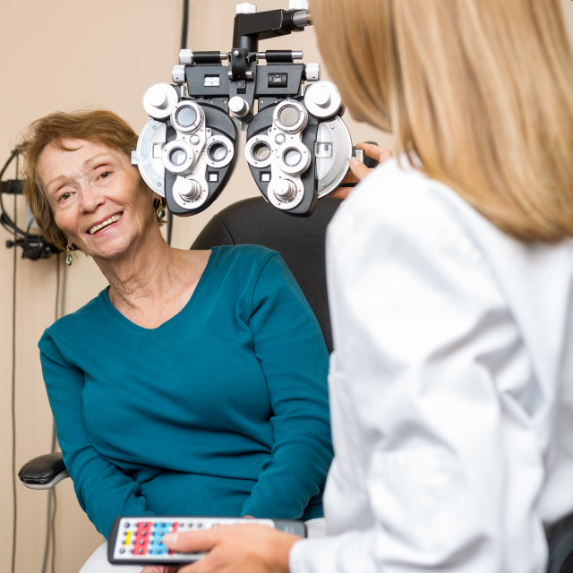 """Smiling Senior Woman Undergoing Eye Checkup"" stock image"
