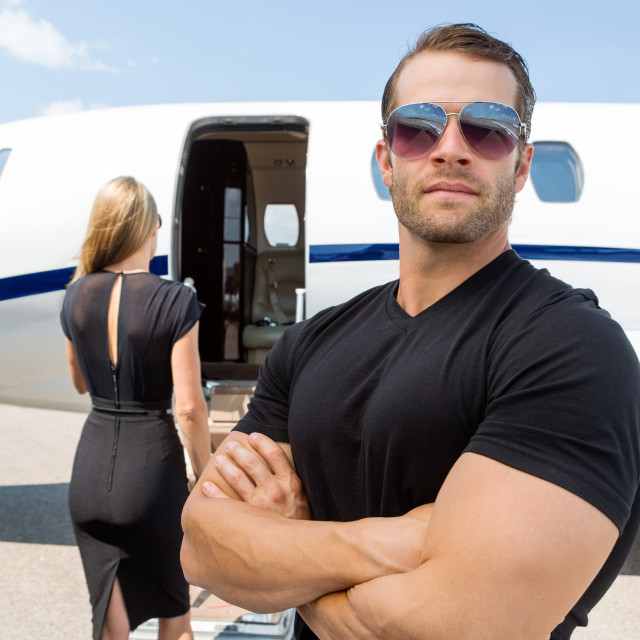 """""""Bodyguard Standing Against Woman And Private Jet"""" stock image"""