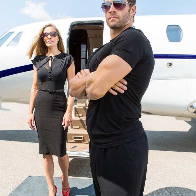 """""""Bodyguard Standing Against Elegant Woman And Private Jet"""" stock image"""