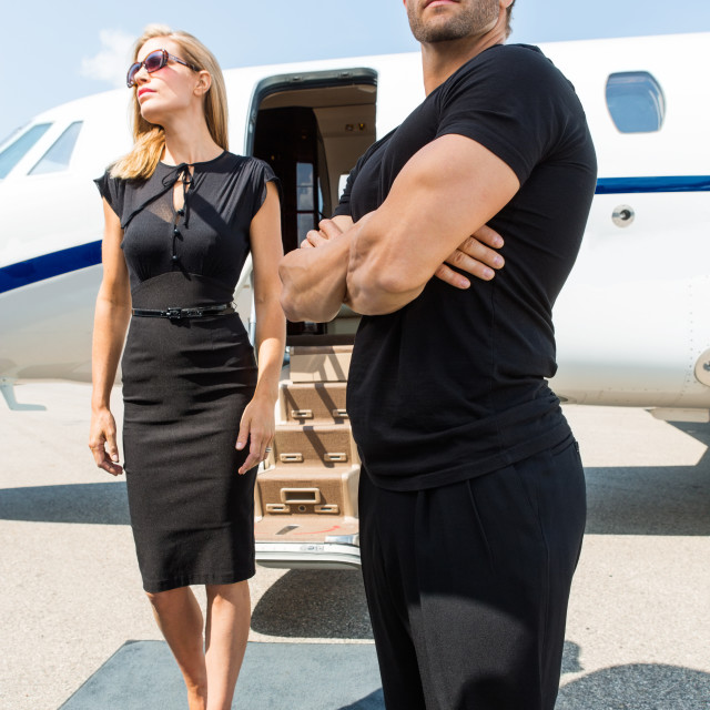"""""""Woman With Bodyguard Against Private Jet"""" stock image"""