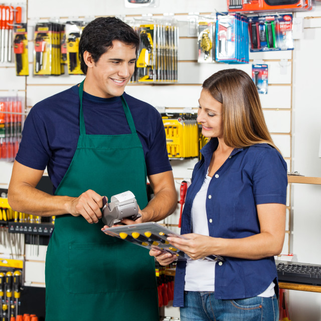 """""""Woman Holding Screwdriver Set With Worker Swiping Credit Card"""" stock image"""
