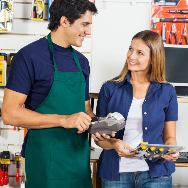 """""""Woman Looking At Worker Swiping Credit Card"""" stock image"""
