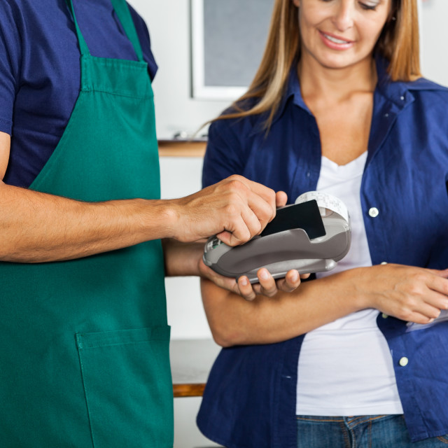 """""""Worker Swiping Credit Card With Woman Holding Screwdriver Set"""" stock image"""