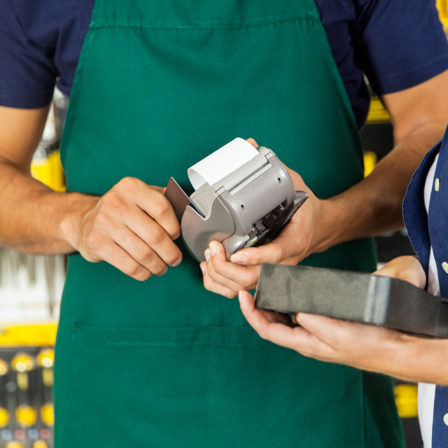 """""""Worker Swiping Credit Card With Woman Holding Tool Set"""" stock image"""