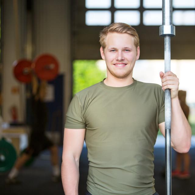 """Athlete Holding Weightlifting Bar At Gym"" stock image"