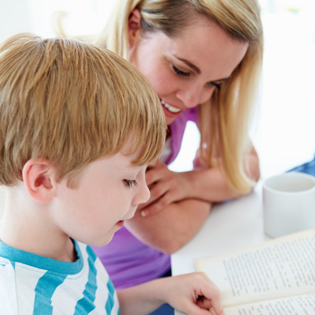 """Mother Helping Son With Homework In Kitchen"" stock image"