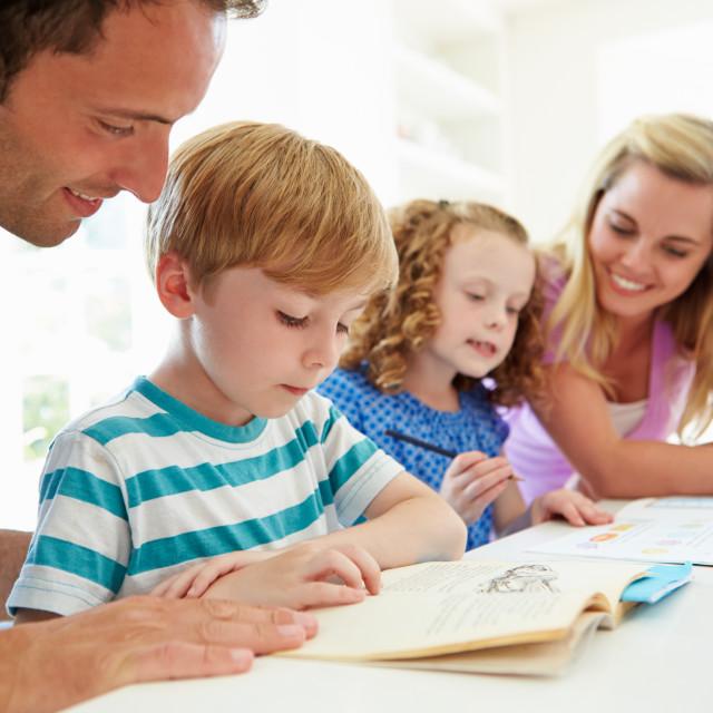 """Parents Helping Children With Homework In Kitchen"" stock image"
