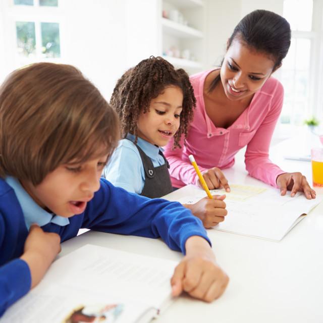 """Mother Helping Children With Homework In Kitchen"" stock image"
