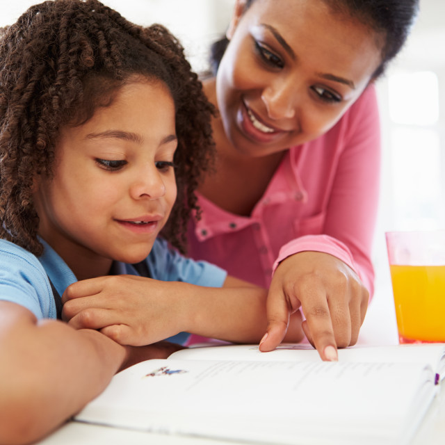 """Mother Helping Daughter With Homework In Kitchen"" stock image"