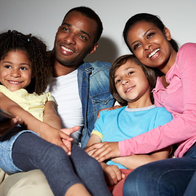 """""""Family Sitting On Sofa Watching TV Together"""" stock image"""