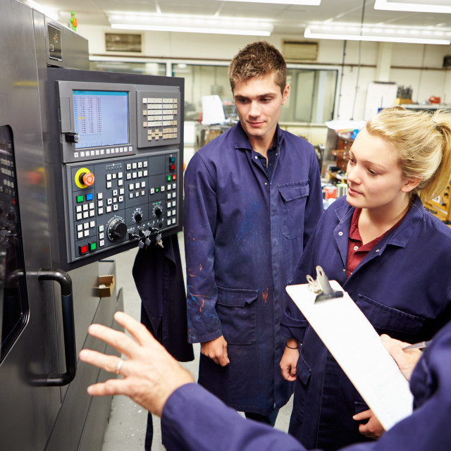 """Engineer Teaching Apprentices To Use Computerized Lathe"" stock image"
