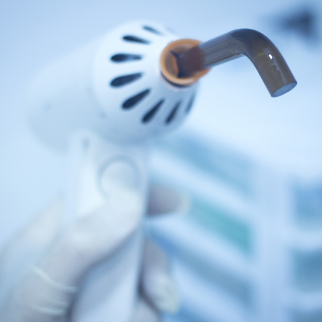 """Dental filling gun in dentist hand in clinic office"" stock image"