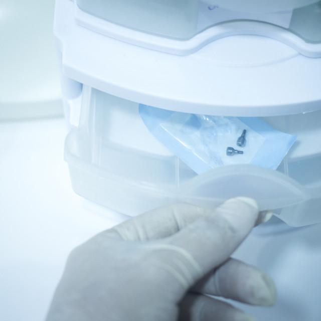 """Dentist hand in glove preparing dental operation drawer"" stock image"