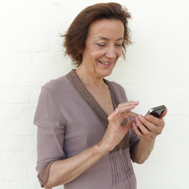 """""""Mature woman smiling and texting"""" stock image"""