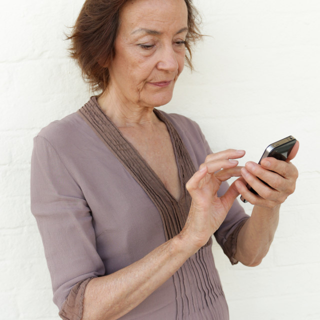 """""""Mature woman annoyed with her phone"""" stock image"""