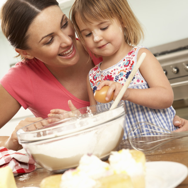 """Young Girl Helping Mother To Bake Cakes In Kitchen"" stock image"