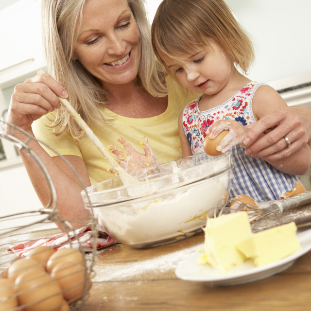 """Young Girl Helping Grandmother To Bake Cakes In Kitchen"" stock image"