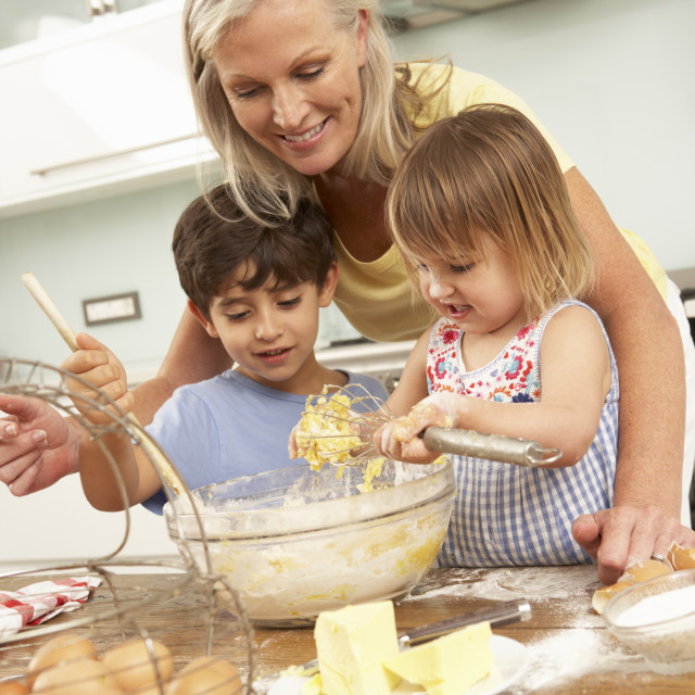 """Grandchildren Helping Grandmother To Bake Cakes In Kitchen"" stock image"