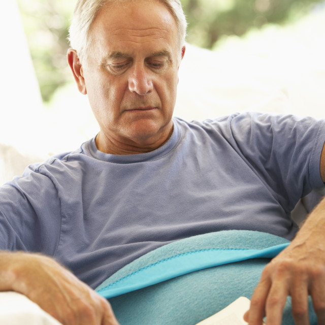 """Senior Man Feeling Unwell Resting Under Blanket"" stock image"