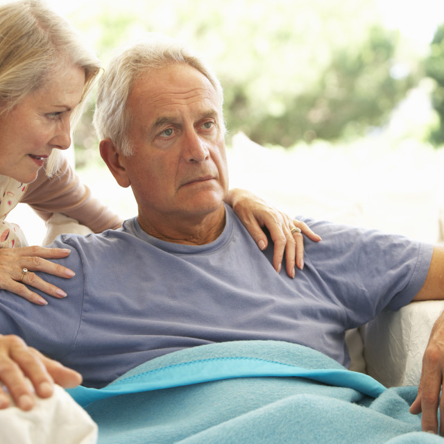 """Wife Comforting Senior Man Feeling Unwell Resting Under Blanket"" stock image"
