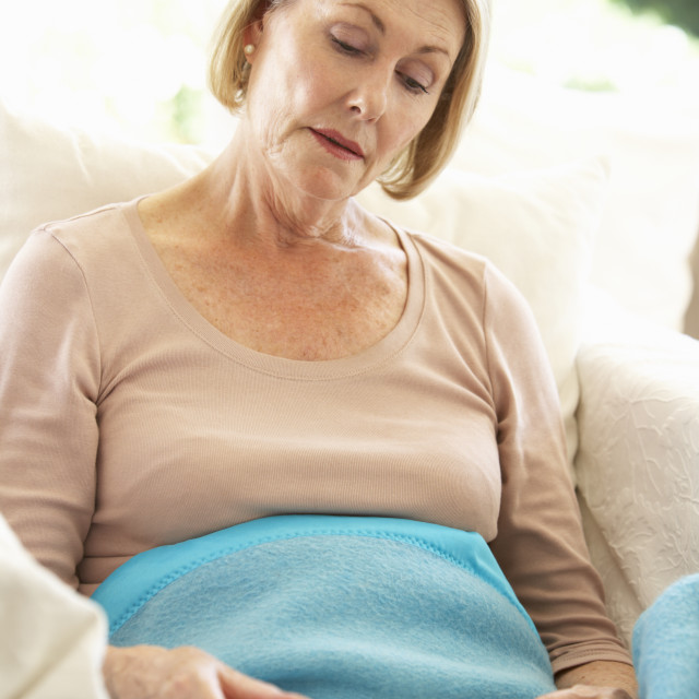 """Senior Woman Feeling Unwell Resting Under Blanket"" stock image"