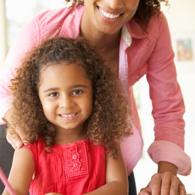 """Mother Helping Daughter With Homework At Home"" stock image"