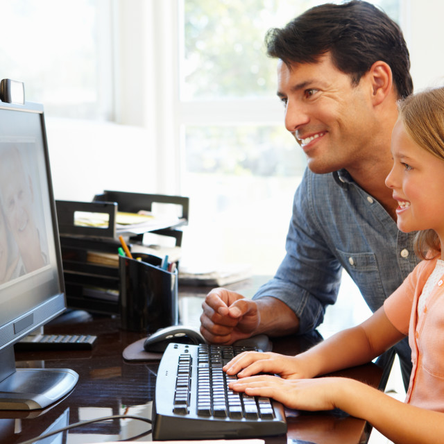 """Father and daughter using skype in home office"" stock image"