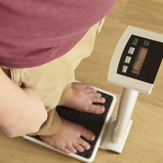 """""""Man standing on digital scales cropped waist down"""" stock image"""