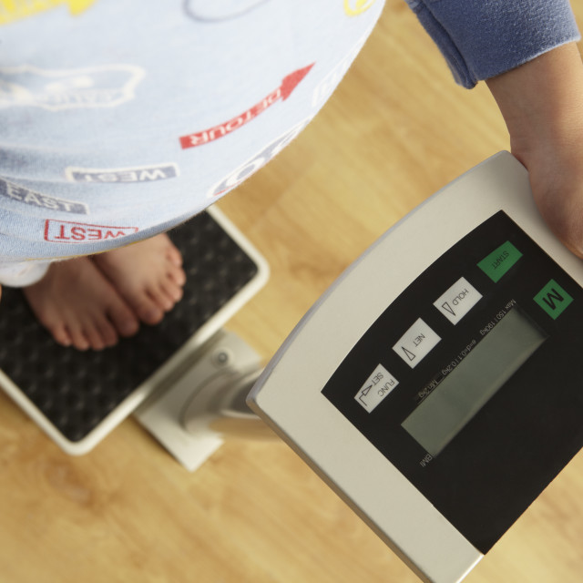 """""""Young boy standing on digital scales cropped waist down"""" stock image"""