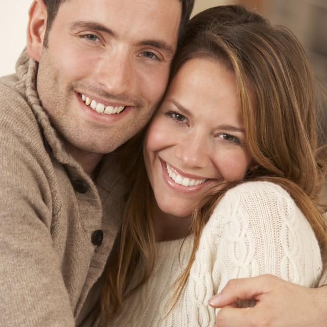 """Portrait 30s couple hugging indoors"" stock image"