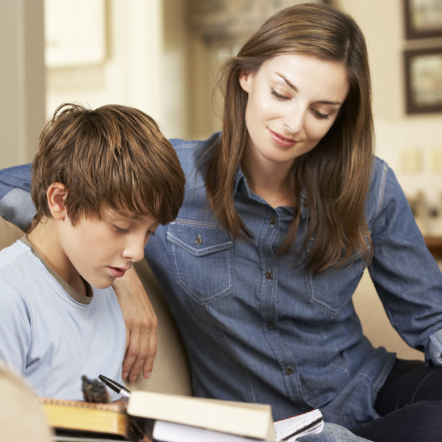 """Mother Helping Son With Homework Sitting On Sofa At Home"" stock image"
