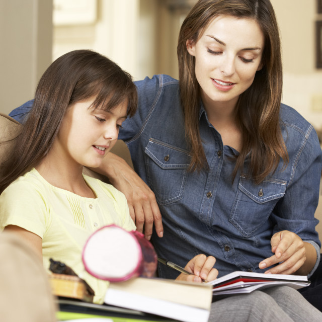 """""""Mother Helping Daughter With Homework Sitting On Sofa At Home"""" stock image"""