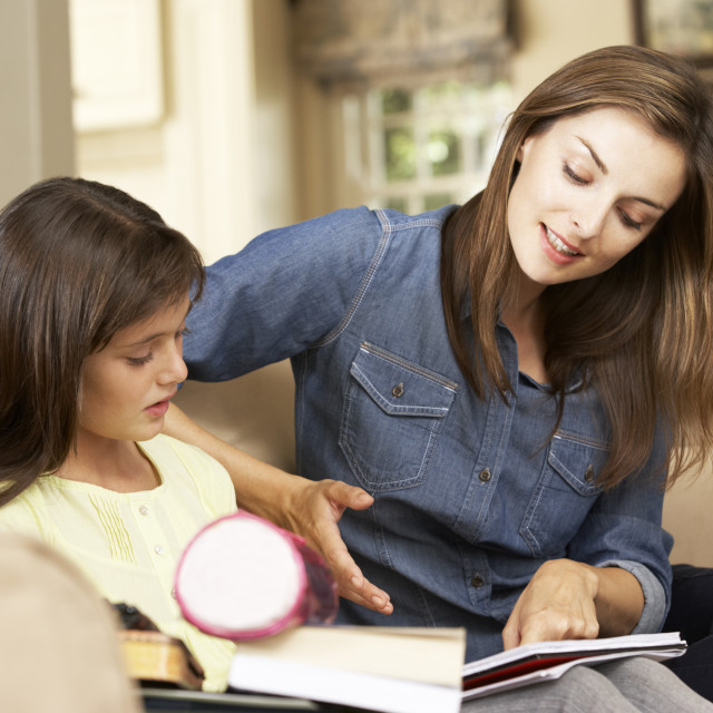 """Mother Helping Daughter With Homework Sitting On Sofa At Home"" stock image"
