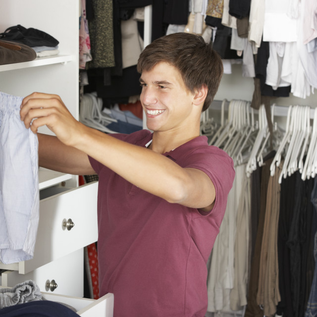 """Teenage Boy Choosing Clothes From Wardrobe In Bedroom"" stock image"