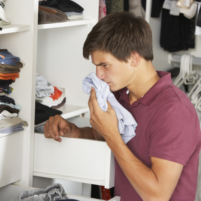 """Teenage Boy Checking Freshness Of Clothes In Wardrobe"" stock image"