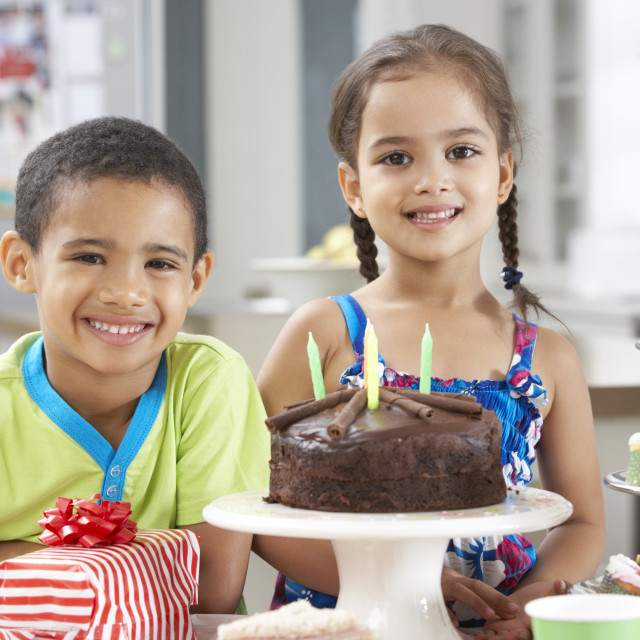 """Two Children Standing By Table Laid With Birthday Party Food"" stock image"