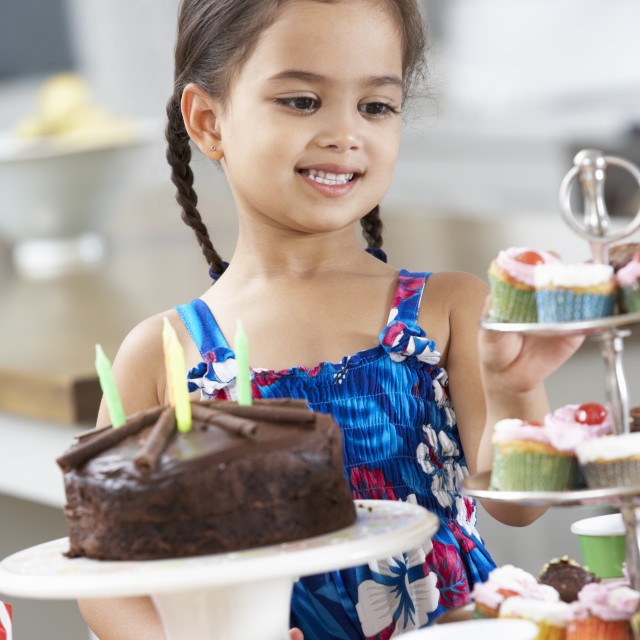 """Young Girl Standing By Table Laid With Birthday Party Food"" stock image"