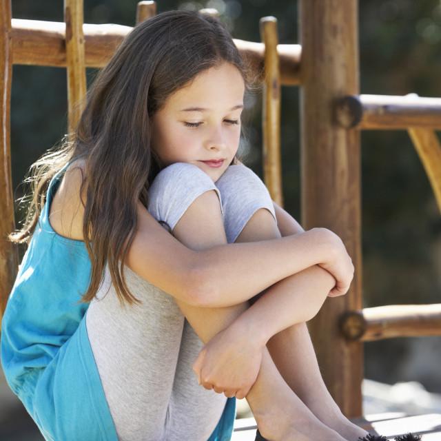 """Sad Young Girl Sitting On Climbing Frame"" stock image"