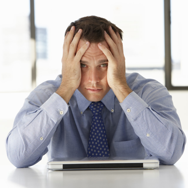 """""""Frustrated Businessman Sitting At Desk In Office Using Laptop"""" stock image"""