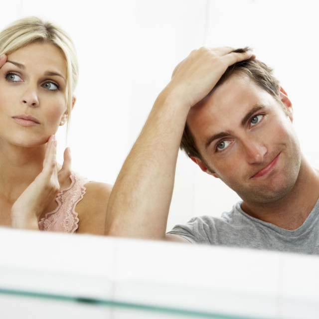 """""""Couple Looking At Reflections In Mirror For Signs Of Ageing"""" stock image"""