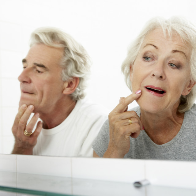"""""""Senior Couple Looking At Reflections In Mirror For Signs Of Ageing"""" stock image"""