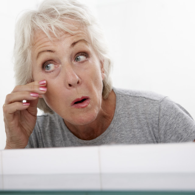 """""""Senior Couple Woman Looking At Reflection In Mirror For Signs Of Ageing"""" stock image"""