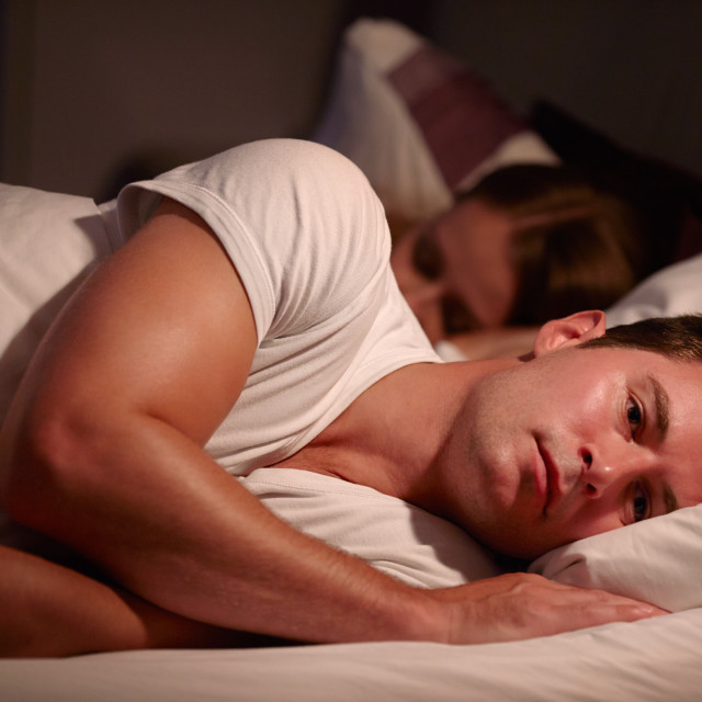"""Man Lying Awake In Bed Suffering With Insomnia"" stock image"