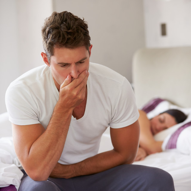 """Man Sitting On Bed And Feeling Unwell"" stock image"
