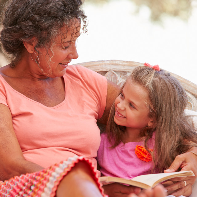 """Grandmother With Granddaughter Reading Book In Garden"" stock image"