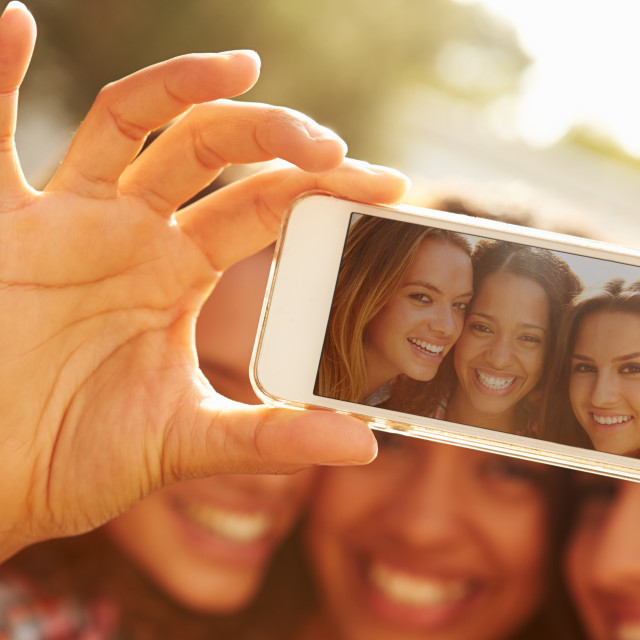 """Female Friends On Holiday Taking Selfie With Mobile Phone"" stock image"