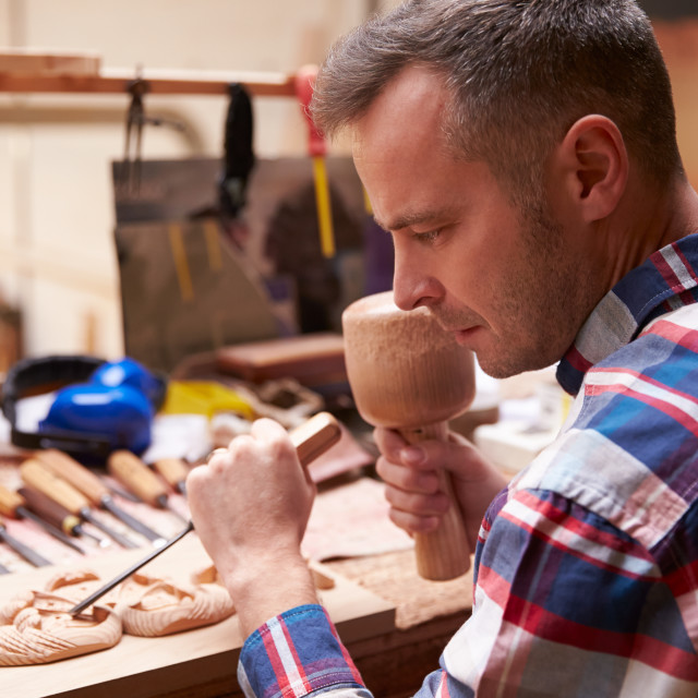 """Carpenter Carving Wood Using Chisel"" stock image"