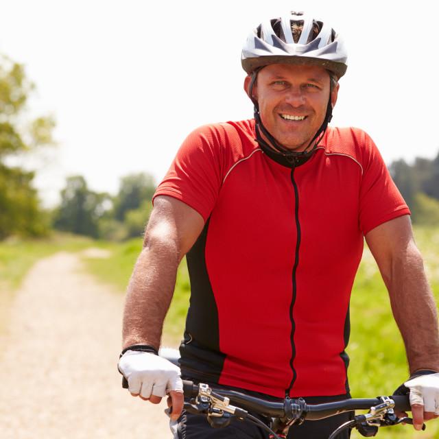 """Man Riding Mountain Bike Along Path In Countryside"" stock image"