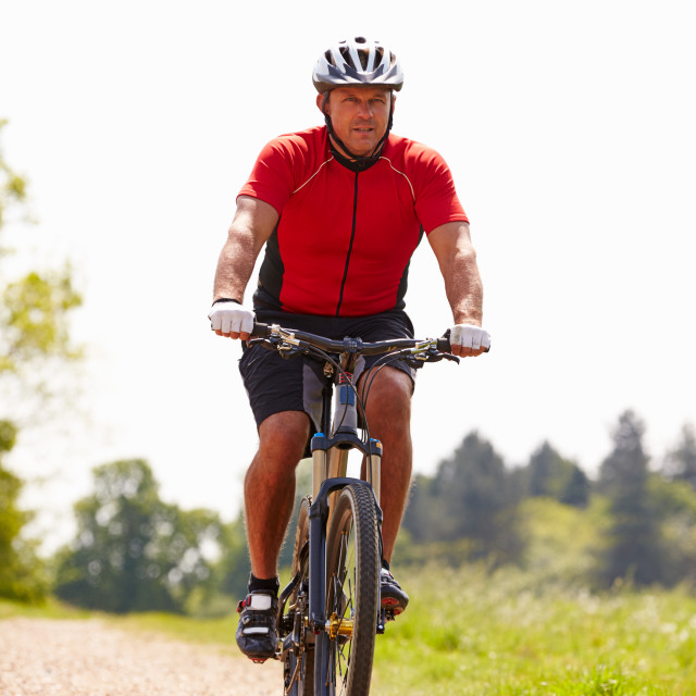 """Man Riding Mountain Bike Along Path In Countryside"" stock image"